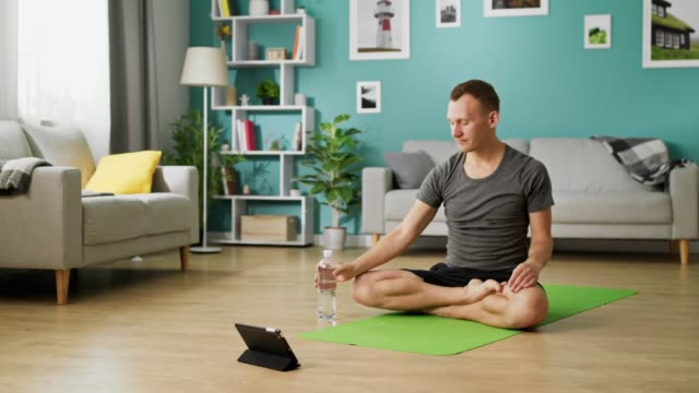 Man drinking water from a bottle during yoga classes online video