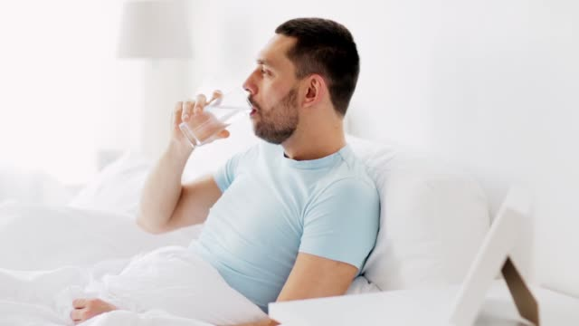 man drinking water in bed at home