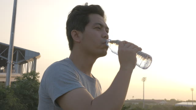 Man drinking water in bottle outdoors jogging video