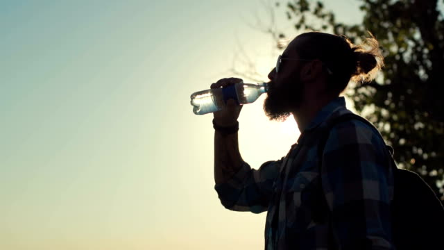 Man drinking water in sunlight Side view of stylish man with backpack drinking water from bottle on background of sunlight and nature. Slow motion. thirsty stock videos & royalty-free footage