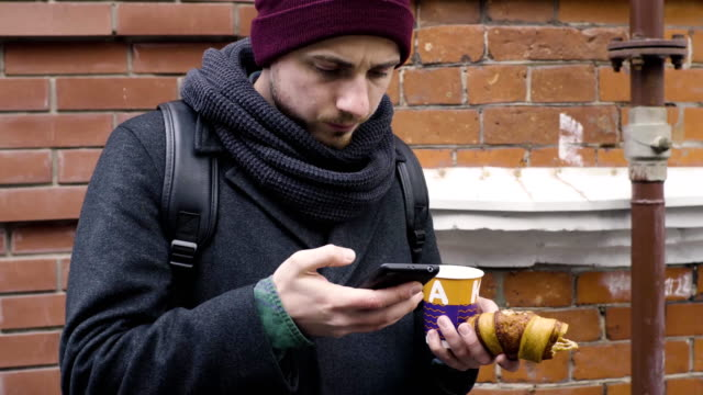 A man drinks coffee and use smartphone standing near a house in the alley video