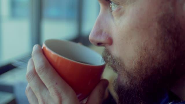 vidéos et rushes de homme boissons un café, tout en travaillant dans le bureau de démarrage - thé boisson chaude