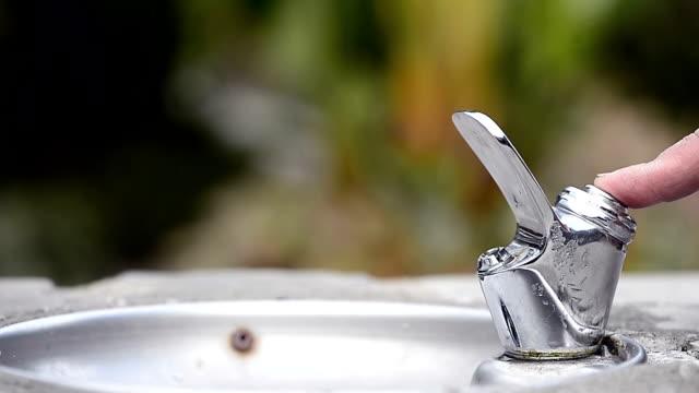 vidéos et rushes de l'homme boit de l'eau de la fontaine - fontaine
