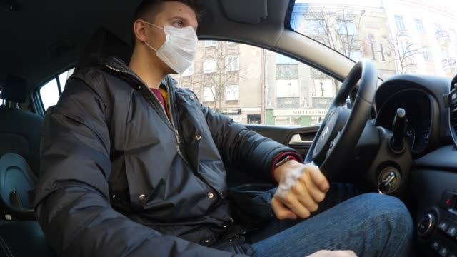 Man Drive Car Wearing Medical Face Mask To Protect From Infection Of Viruses, Pandemic, Air Pollution, Hazardous Particles. Threat Of Coronavirus