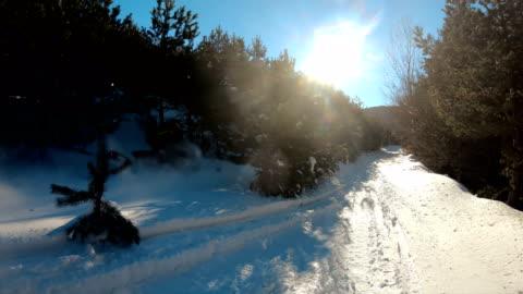 vidéos et rushes de l'homme conduisent la motoneige dans les montagnes. personnel de la station de ski. conduite extrême avec un paysage hivernal parfait. neige à cheval au sommet - format hd