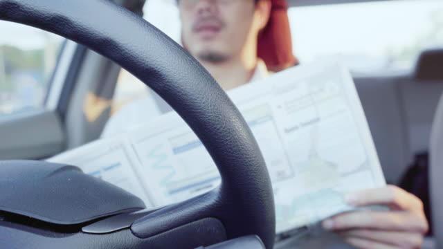 車の中で4kマンドライバー読書雑誌は、オートパイロットモードを使用しています。自動運転車 - 自動運転車点の映像素材/bロール