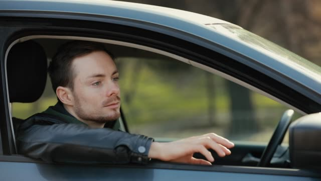 Man driver sitting in a car waiting while pounding fingers video