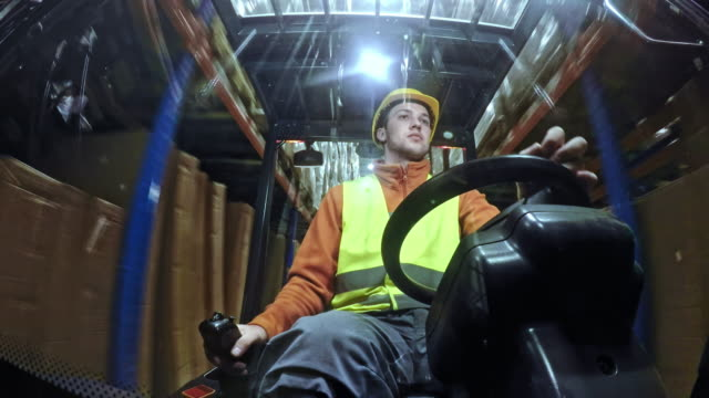 LD Man driving a forklift in the warehouse Wide low angle locked down shot of a man driving a forklift in the warehouse between the pallet racks. Shot in Slovenia. forklift stock videos & royalty-free footage