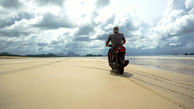 Man driving a motorcycle on beach video