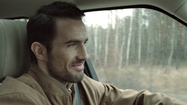 Man driving and smiling Portrait of handsome man driving a car during an autumn rainy day. Side view. handsome people stock videos & royalty-free footage