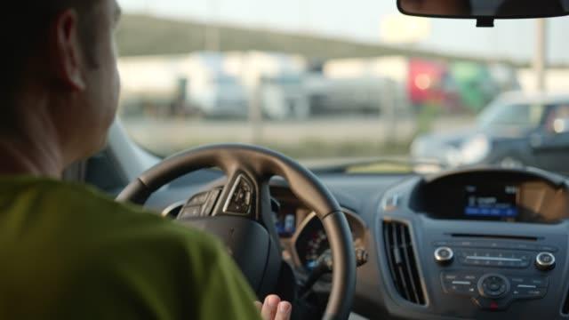 vidéos et rushes de homme conduisant et tournant sur une voiture dans la ville de coucher du soleil. les rayons du soleil brillent à travers le pare-brise - voiture