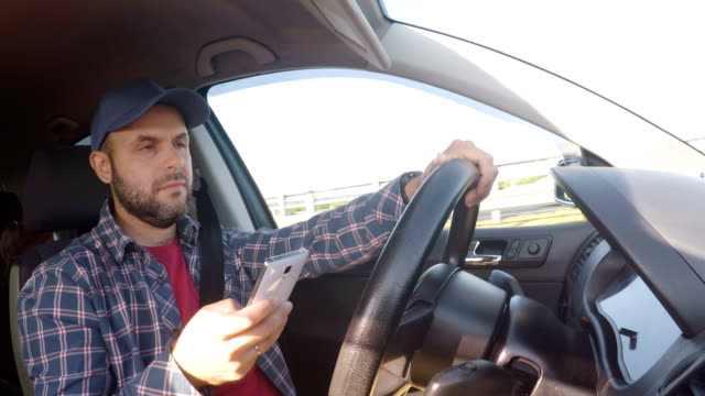 man driving car on highway and texting on smartphone.  man with mobile telephone, driver with cell phone, driving car on street, using smartphone text messaging and internet. danger and risk on road - niebezpieczeństwo filmów i materiałów b-roll