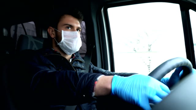 man driving car with face mask and glove. prevention for coronavirus. - autista mestiere video stock e b–roll