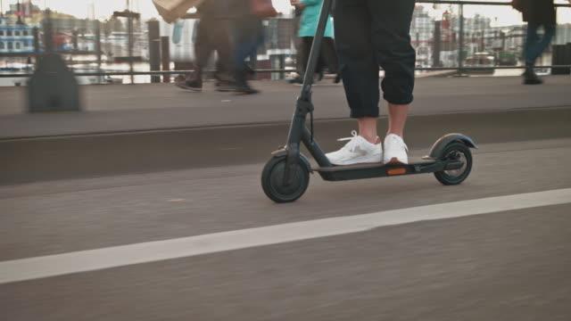 man driving electric push scooter on bridge - monopattino elettrico video stock e b–roll