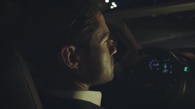 Man driving luxury car at night video