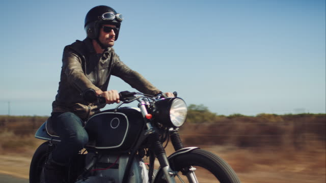 Man driving on his motorcycle on highway Man driving on his motorcycle on a highway. Its a long and straight road through a desert like surrounding. He has a retro style bike and is wearing a leather jacket and a helmet. motorcycle stock videos & royalty-free footage