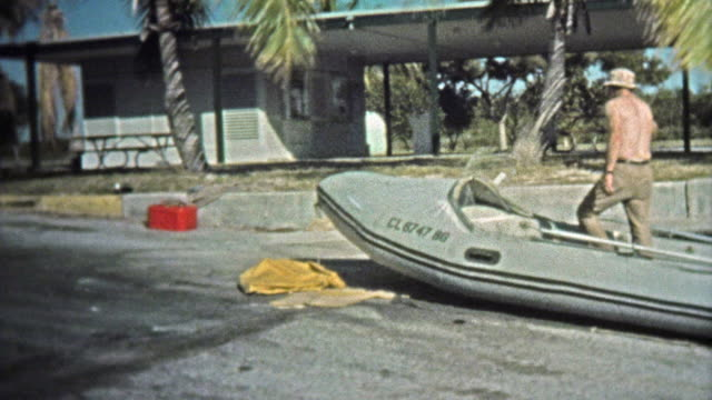 KEY WEST, FL, USA -1973: Man driving professional inflatable boat around harbor with pelicans. video