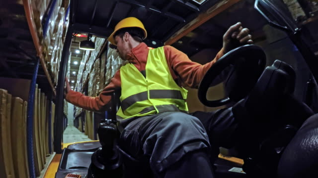 LD Man driving the forklift backwards in the warehouse aisle Wide low angle locked down shot of a man driving a forklift in the warehouse. Shot in Slovenia. forklift stock videos & royalty-free footage