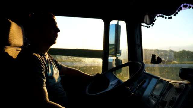 man driving truck and carefully watching the road traffic. caucasian guy is riding through the countryside on the sunset background. profile of lorry driver inside the cab. slow motion close up - тягач с полуприцепом стоковые видео и кадры b-roll