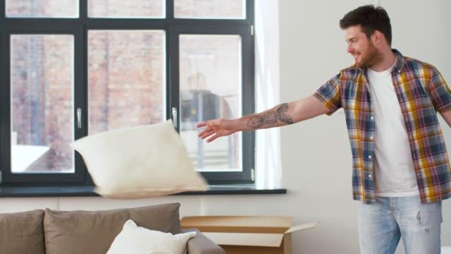 man dropping pillows and jumping to sofa at home - vídeo