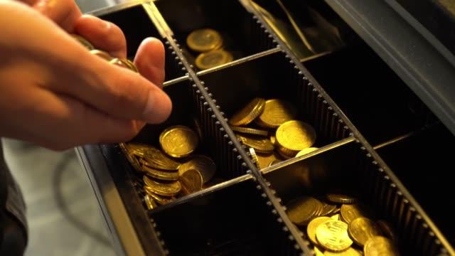 Man drops coins into cash register