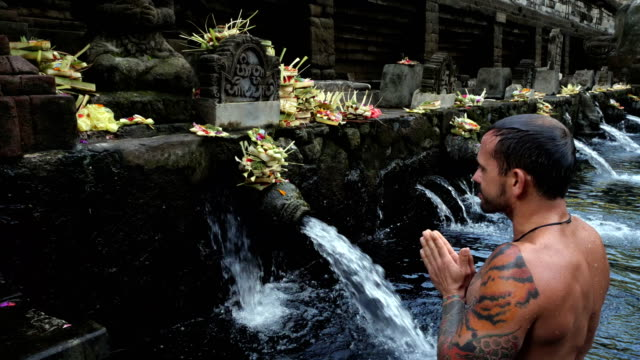 man during ceremony in tirtha empul temple (holy spring water temple) in bali - tempio video stock e b–roll