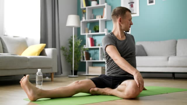 Man during individual training at home relaxing muscles and caring for health video