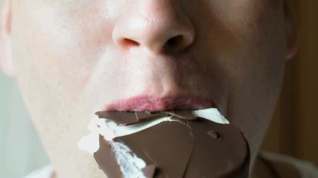 man eating a chocolate ice-cream - mordere video stock e b–roll
