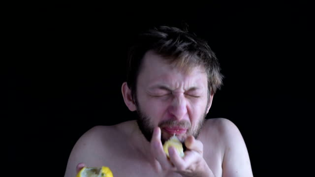 man eating a lemon - gusto aspro video stock e b–roll