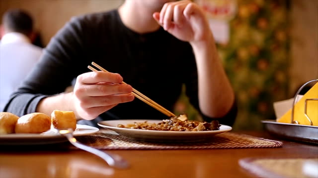 Man eating chinese food with chopsticks in restaurant video