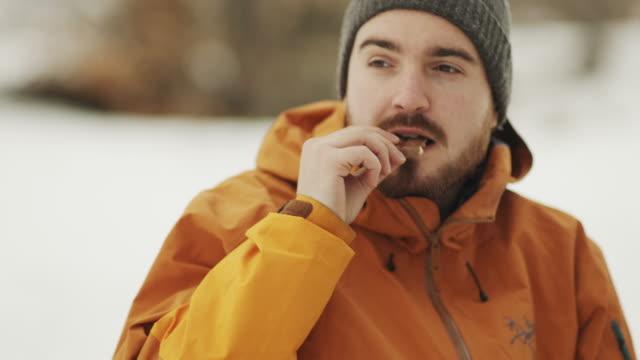 vídeos de stock, filmes e b-roll de homem comendo chocolate na floresta de inverno. vídeo estoque - chocolate