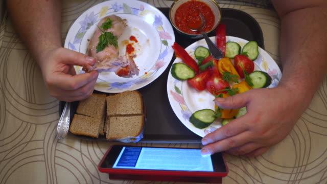 man eating dinner while lying on stomach in bed reading news on digital tablet - taca filmów i materiałów b-roll