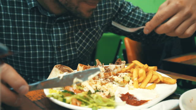 mann isst doner kebab - döner stock-videos und b-roll-filmmaterial