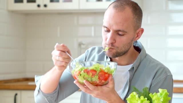 vídeos de stock e filmes b-roll de man eating fresh tasty salad healthy eating - comer