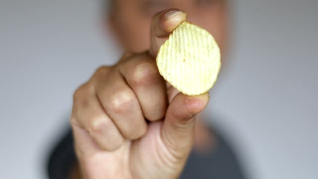 Man eating one potato chip - close up Man shows one potato chip to camera and then eats potato chip potato chip stock videos & royalty-free footage