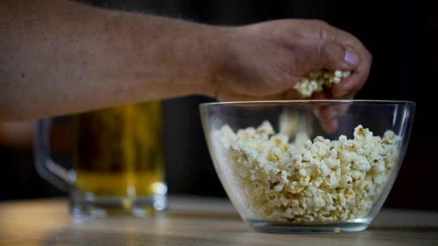 man eating popcorn and drinking a beer while watching movie at home, close-up - вредное питание стоковые видео и кадры b-roll