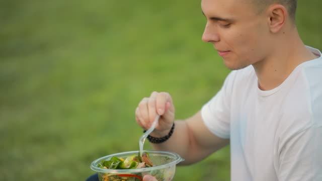 vídeos de stock e filmes b-roll de man eating salad sitting on grass - saladeira