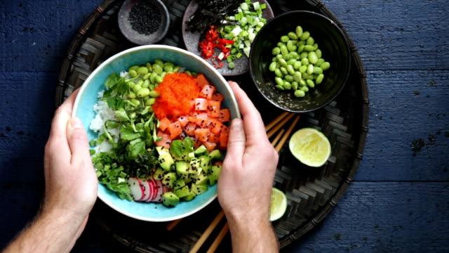 Man eating Salmon poke bowl Poke bowls with salmon, tobiko red, avocado, edamame, vegetables, sprouts and rice on dark blue background sashimi stock videos & royalty-free footage