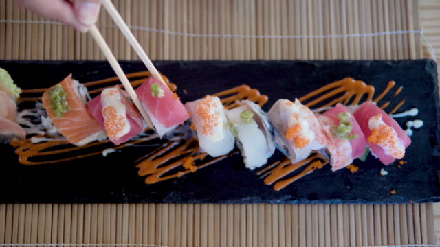 vídeos y material grabado en eventos de stock de hombre comiendo sushi en el restaurante japonés. - comida gourmet