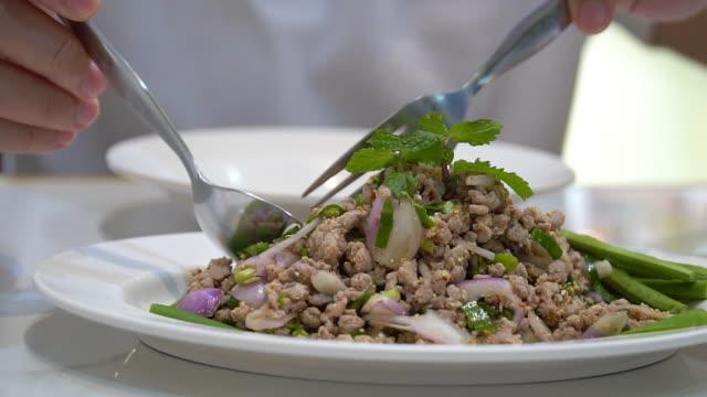 vídeos de stock, filmes e b-roll de o homem que come o alimento tailandês picou a carne de porco (larb e-san). - nordeste