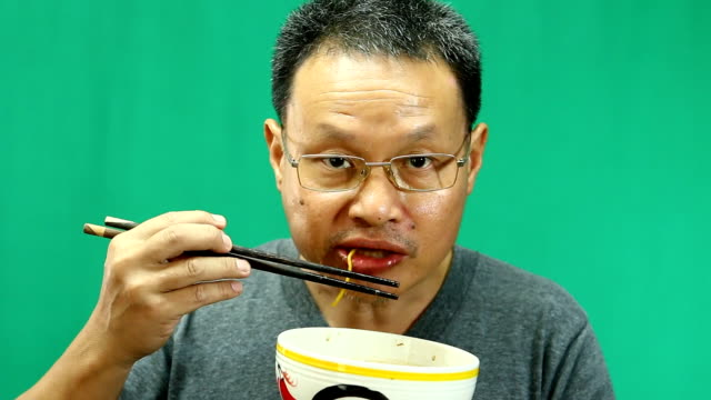 man eating yellow noodle with green background video