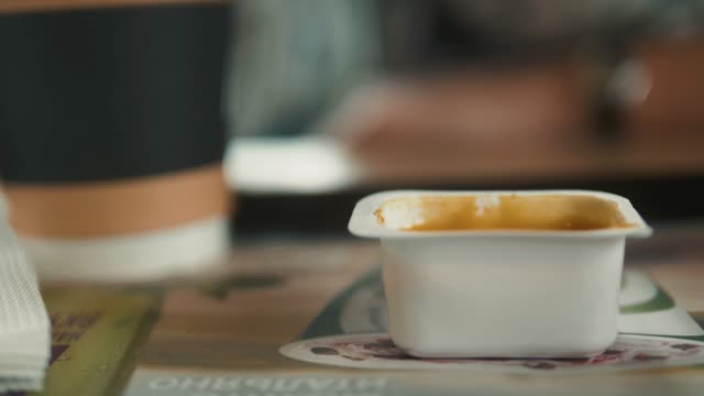 Man eats French fries, dipping it in cheese sauce. Close-up hands in fast food restaurant cafe, fat food