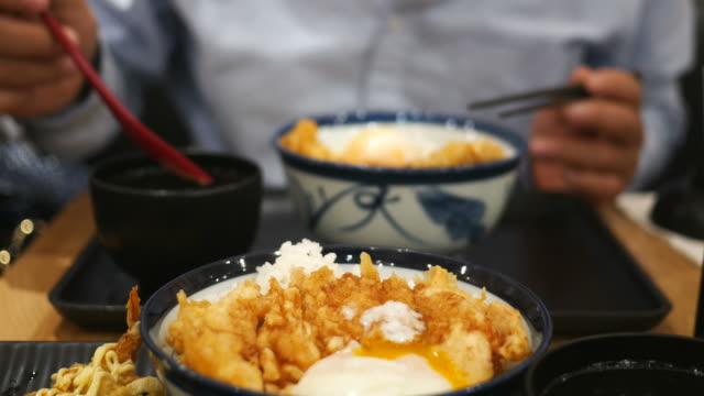 vídeos de stock e filmes b-roll de man eats japanese food - comida asiática