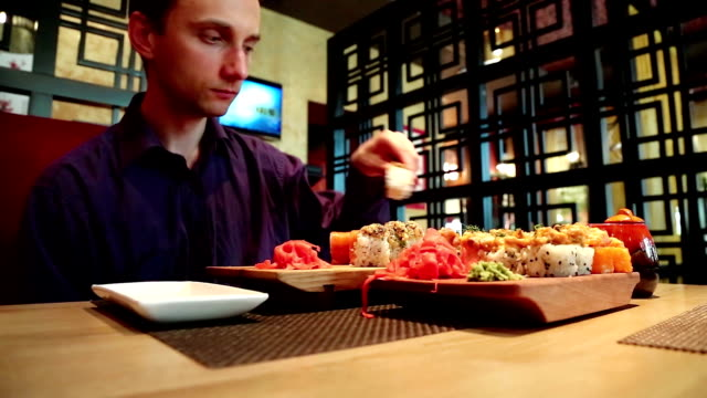Man eats sushi in japanese restaurant video