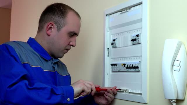 クライアントを家のサーキット ・ ブレーカーの電気仕事を男します。fullhd - 電気工点の映像素材/bロール