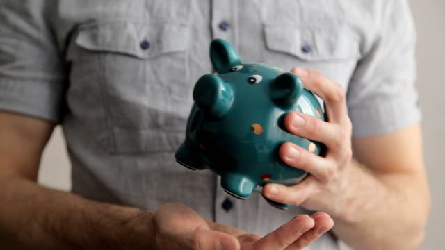 Man empties a piggy bank, last few coins falls. Last money, end of savings, crisis, bankruptcy Man empties a piggy bank, last few coins falls. Last money, end of savings, crisis, bankruptcy piggy bank stock videos & royalty-free footage