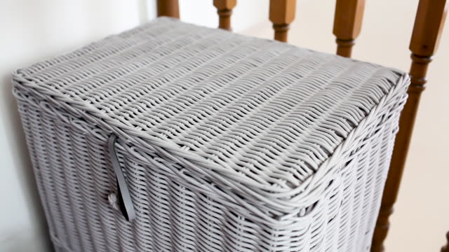 Man emptying laundry bin into washing basket Video of a man taking shirts out of wicker laundry basket on a landing and putting them into a blue plastic laundry basket laundry basket stock videos & royalty-free footage