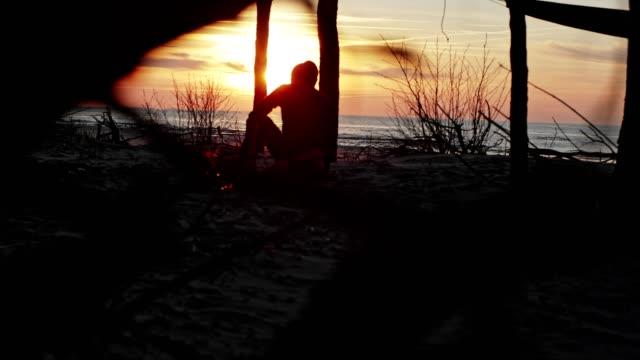 vidéos et rushes de homme appréciant le feu de joie sur un camp de plage - étendue sauvage scène non urbaine