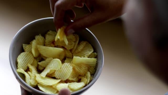 Man enjoying eating potato chips - over the shoulder Over the shoulder view of man eating potato chips potato chip stock videos & royalty-free footage