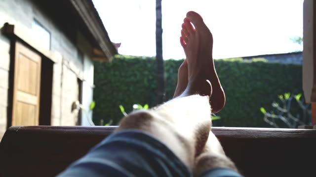 vidéos et rushes de l'homme jouissant sur un canapé à la maison porche. - boisson chaude
